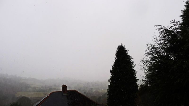 The view out of the studio windows, snow obscuring the valley