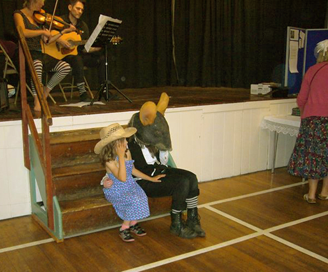 The Dormouse listening to a child's secrets, while Howard & his cousin Beckie play music behind them.